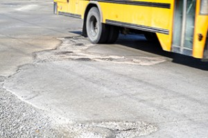 A school bus travels over bumpy roads. Vote yes for safe roads on May 5.