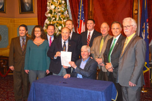 The League's Chris Hackbarth and League Member and Big Rapids Mayor Mark Warba (green tie) joined Governor Rick Snyder in signing HB 4578.